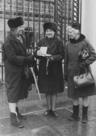 Connie Ford (with her two sisters) holding her MBE, 1970