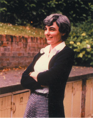 Margaret Lucas, standing with her arms folded, looking away from camera and smiling.