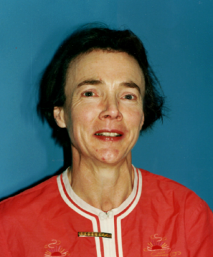 Image of Janet Devoy looking into camera. She is wearing a mainly red top and is standing against a blue background.