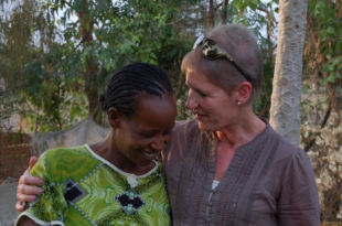 Image of a lady with her arm around another lady with trees in the background, both smiling.