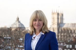 Image of a lady wearing a blue blazer over a white shirt looking at the camera with a London city-scape in the background, including the Houses of Parliament.