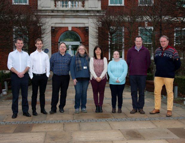 Five gentlemen and three ladies standing in front of APHA Weybridge