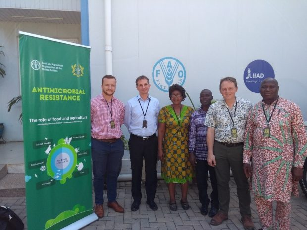 Five gentlemen and one lady standing in front of a pull-up banner sign to their left saying, Antimicrobial Resistance, the role of food and agriculture.