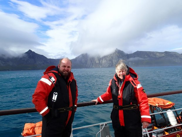 Picture of Jill and a South Georgia biosecurity officer on a boat with mountains and clouds behind them.