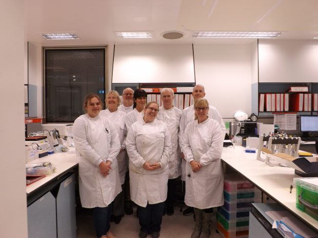 Image of eight laboratory scientists standing together for a photograph.