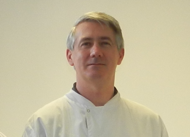 Male scientist wearing a lab coat and looking into camera