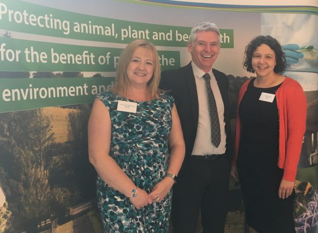 Two female and one male APHA Heads of Department posing for a photograph together in front of an APHA banner saying 'promoting animal, plant and bee health'