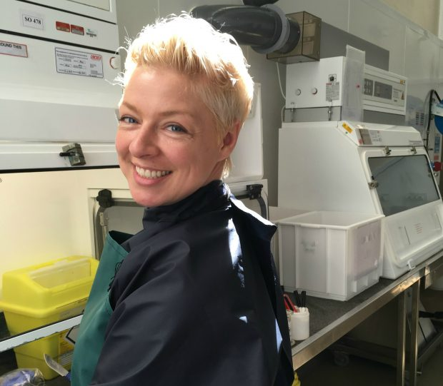 Female veterinary investigation officer standing in a lab at a glass cabinet with a surgical knife in her hand