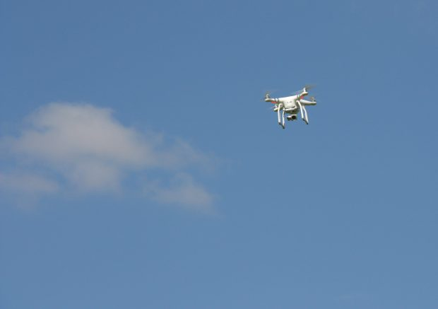 White drone flying against a blue sky