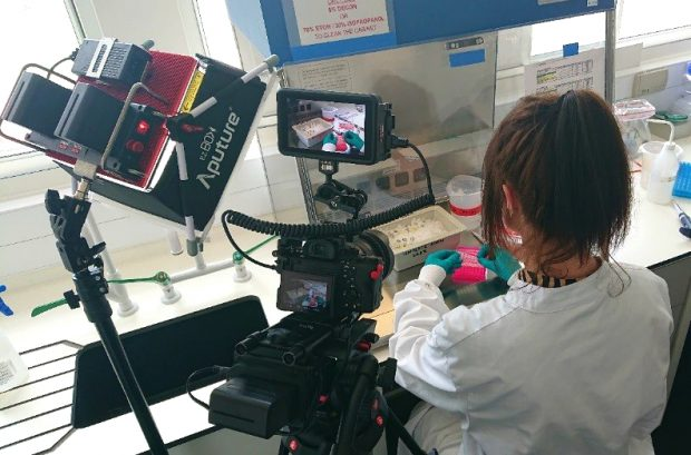 Female scientist performing an experiment while a camera films her from over her shoulder.