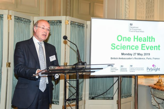 Image of a gentleman in a suit standing at a microphone with a screen behind him showing the words: Department for Environment Food and Rural Affairs, One Health Science Event, Monday 27 May 2019, British Ambassador's Residence, Paris, France.