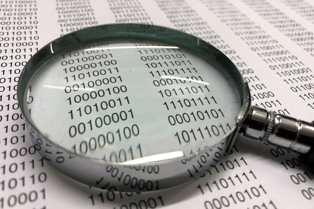 Page of binary code with a magnifying glass laying on the page.