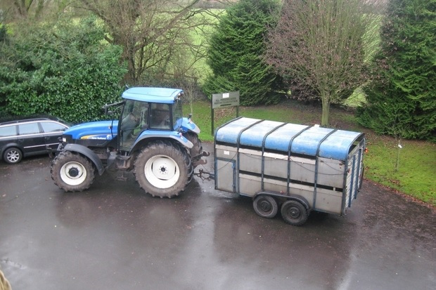 Image of a blue tractor parked on black tarmac towing a large trailer.