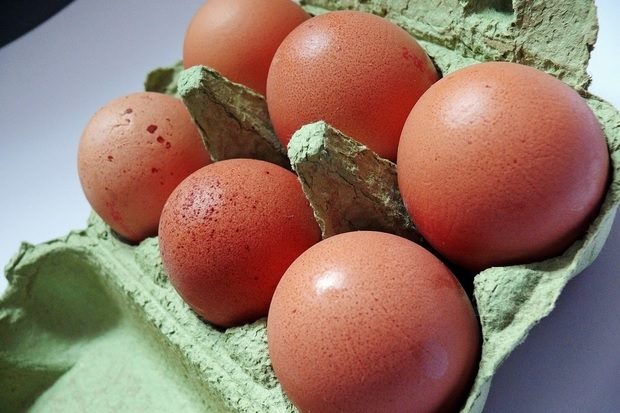 Image of six brown eggs in a green egg box.