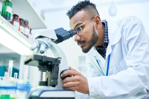 Image of a male scientist looking through a microscope