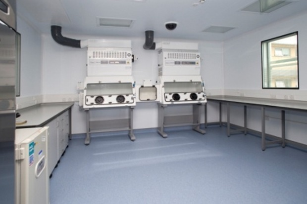 Image of an empty laboratory, showing only some work benches and two glass-fronted cabinets.