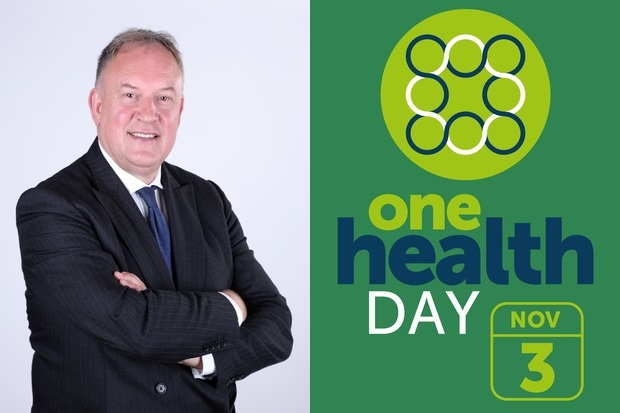 Image of a man in a suit standing with his arms crossed next to the One Health Day logo, November 3