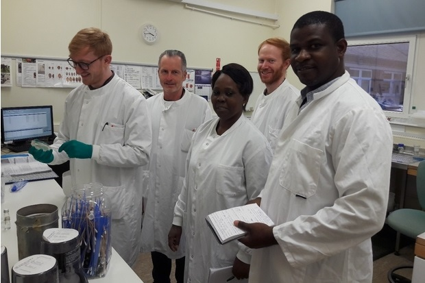 Image of four gentlemen and one lady in white coats standing in a laboratory
