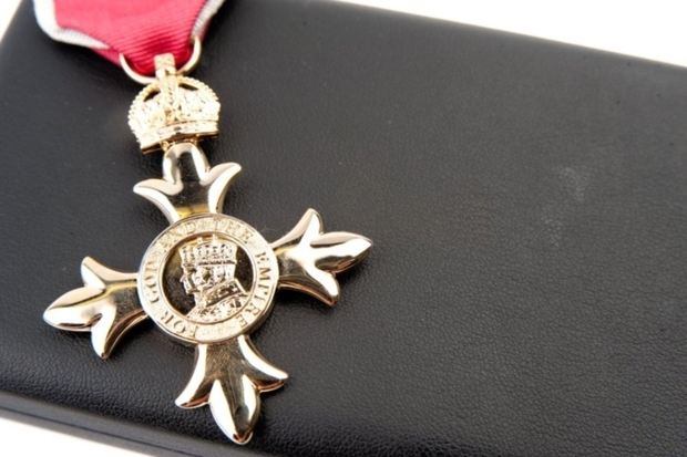 Image of a gold medal with the words 'For God and the Empire' written on it. The medal has a red ribbon and is sitting on a black box.
