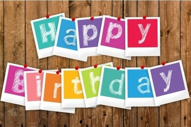Letters spelling out the words 'happy birthday' pinned to a wooden background.